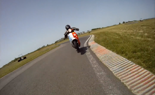 Vespa power wheelie on the racetrack chasing a supermoto.